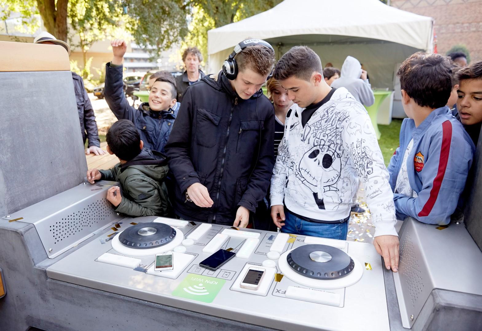 DEN HAAG, 5 oktober 2016. Opening eerste jongerenplek met DJ-functionaliteit en wifi. Wethouder Ingrid van Engelshoven opent de eerste Fono oftewel een dj-draaitafel met gratis wifi op de Robijnhorst in de wijk Mariahoeve. Door een telefoon op de draaitafel te leggen, wordt muziek versterkt en kan eigen muziek gemixt worden. Het maximale volume is voor de buurtbewoners begrensd en 's avonds staat de DJ-tafel uit. Jongerenambassadeurs hadden aangegeven dat zij graag zo'n plek wilde hebben. FOTO MARTIJN BEEKMAN